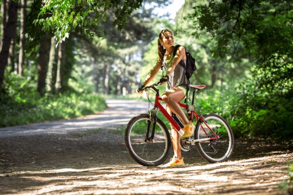 woman riding her bike on a nature trail