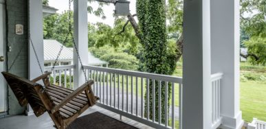 The porch swing on the deck looks over the leafy green lawn