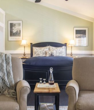 A suite at the inn boasts two cozy chairs, a bottle of water, a fireplace, a plush bed, vaulted ceilings, and a large sunny window.