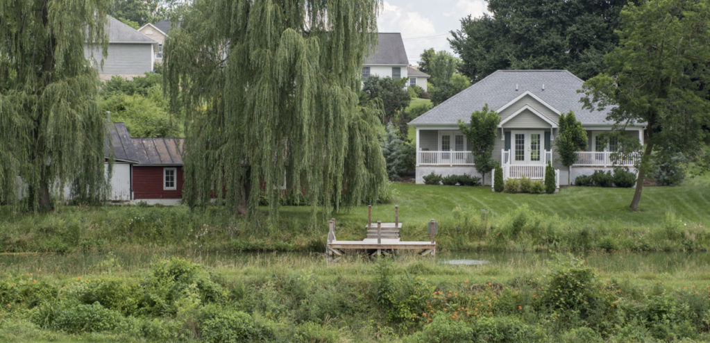 One of the cottages rests by the pond with large willow trees and a dock.